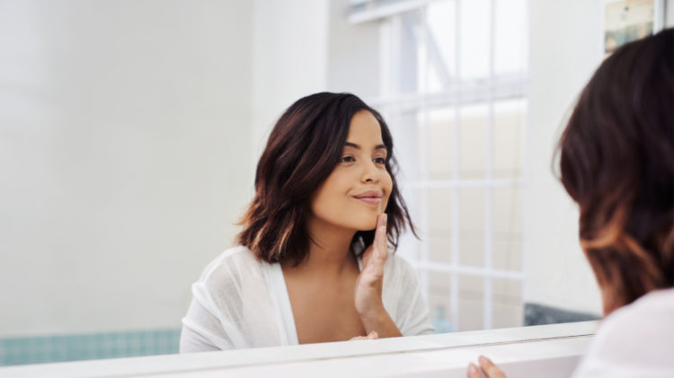 Attractive young woman going through her morning beauty routine in the bathroom