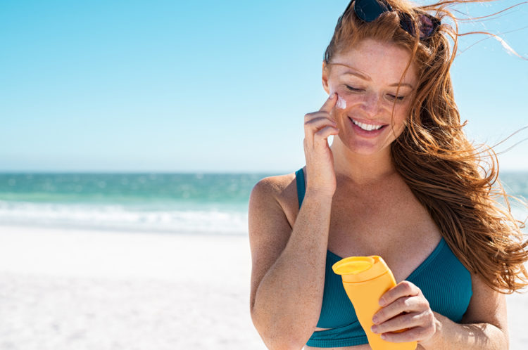 Beautiful young woman in blue bikini at beach applying sunscreen on face for protection on a sunny day. Mature woman with freckles and red hair enjoying summer holiday while applying suntan lotion. Portrait of smiling lady with healthy skin.