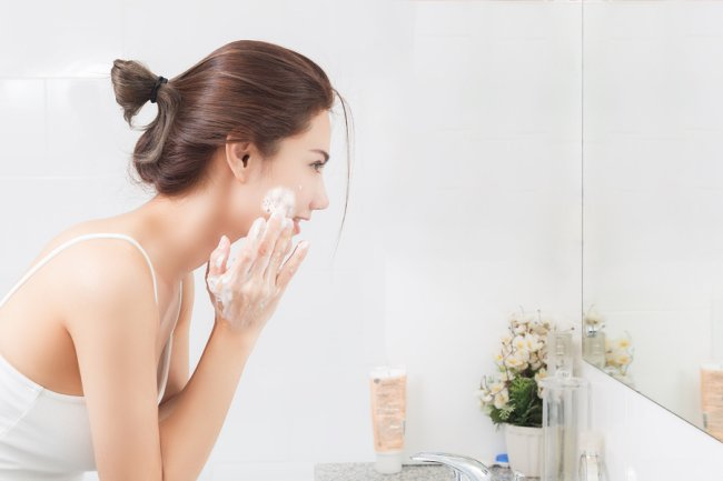 Women washing her face with cream