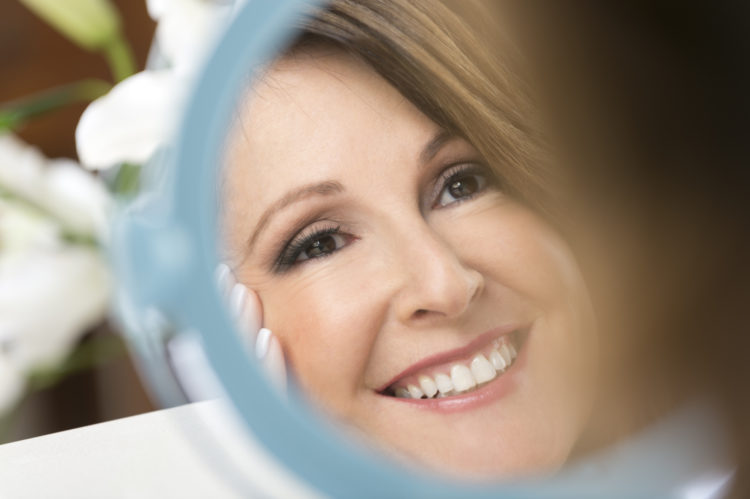 Happy mature woman looking in the mirror. Close-up