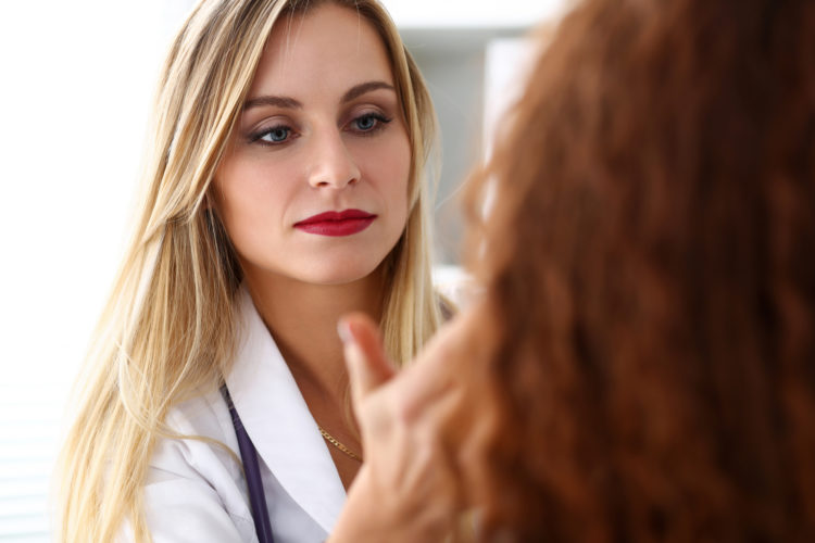 Beautiful female medicine doctor with serious face examine patient. Medical care, illness diagnosing, physical, physician consultation, insurance concept. Dermatologist or oncologist examination