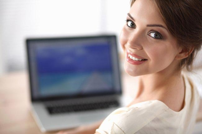 Beautiful woman sitting in front of laptop